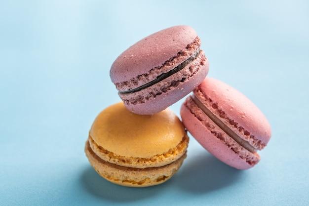 Macarons na superfície azul com foco seletivo de sobremesas francesas coloridas