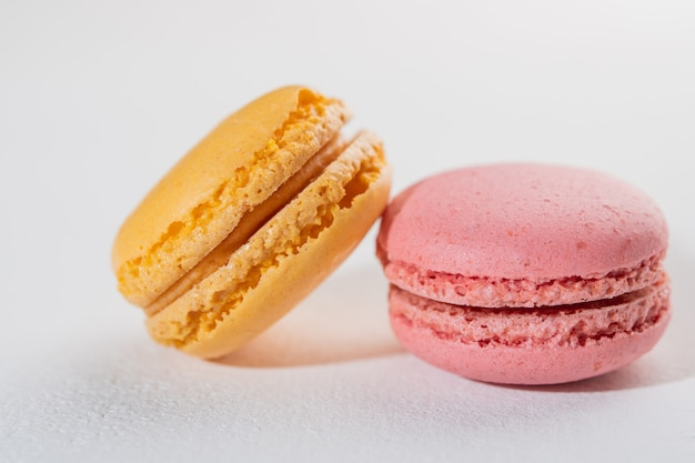 Macarons na superfície branca, sobremesas francesas coloridas, vista superior, foco seletivo