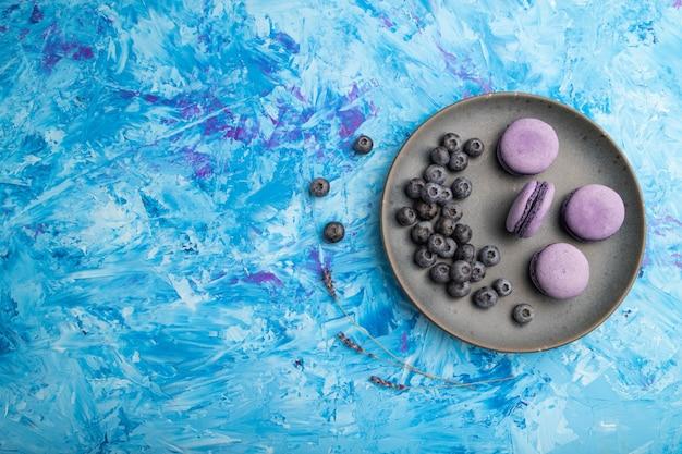 Macarons roxos ou bolos de macarons com mirtilos em um prato de cerâmica em uma superfície de concreto azul