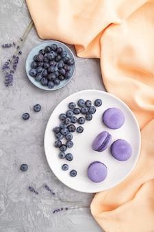 Macarons roxos ou bolos de macarons com mirtilos em uma placa de cerâmica branca em uma superfície de concreto cinza e tecido laranja