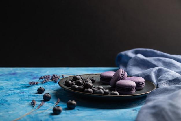 Macarons roxos ou bolos de macaroons com mirtilos na placa de cerâmica. vista lateral, copie o espaço.