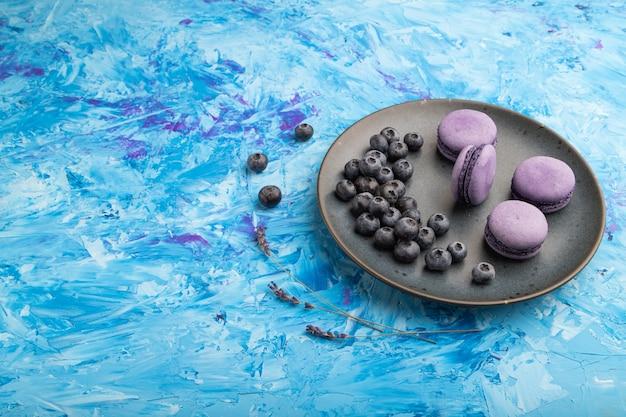 Macarons roxos ou bolos de macaroons com mirtilos no prato de cerâmica