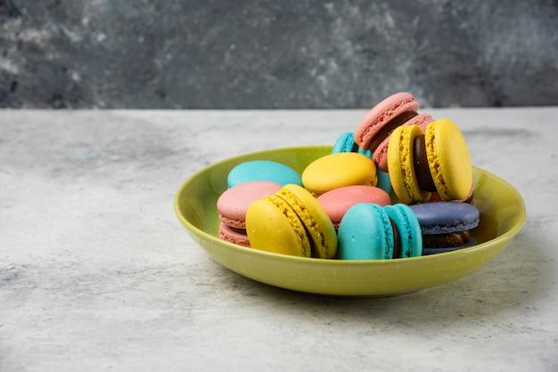 Macarons saborosos coloridos na placa verde e na mesa branca.