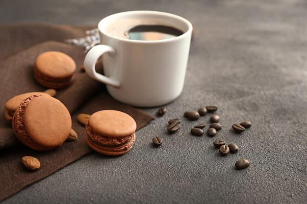 Macarons saborosos com uma xícara de café na mesa cinza