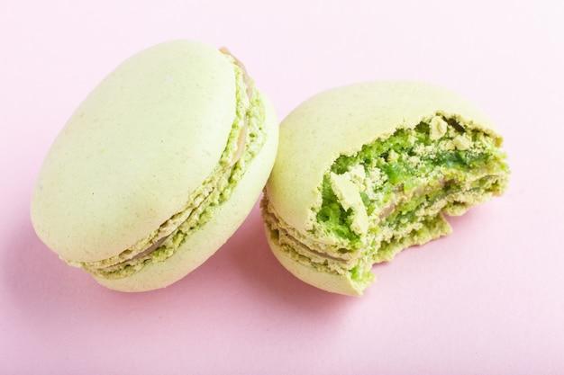 Macarons verdes inteiros e mordidos ou bolos de confeitos em fundo rosa pastel