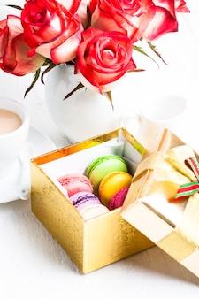 Macaroon em caixa de presente e rosas em vaso