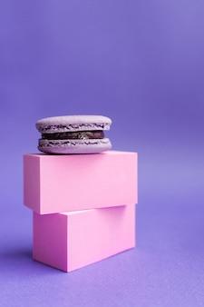 Macaroon roxo em um pedestal. sobremesa francesa para o halloween. produtos de panificação de farinha de amêndoa.