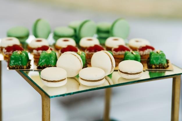 Macaroons brancos servidos com doces verdes em uma barra de chocolate