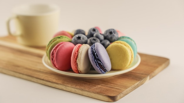 Macaroons coloridos brilhantes e mirtilo no prato redondo, deliciosos bolos de macarons no fundo de madeira