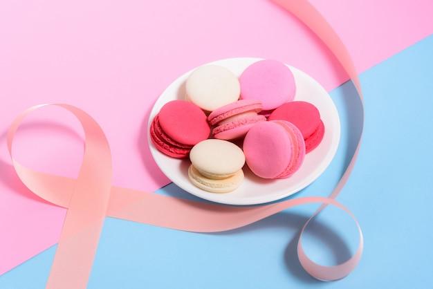 Macaroons coloridos caseiros na placa branca com fita rosa em fundo pastel-de-rosa e azul