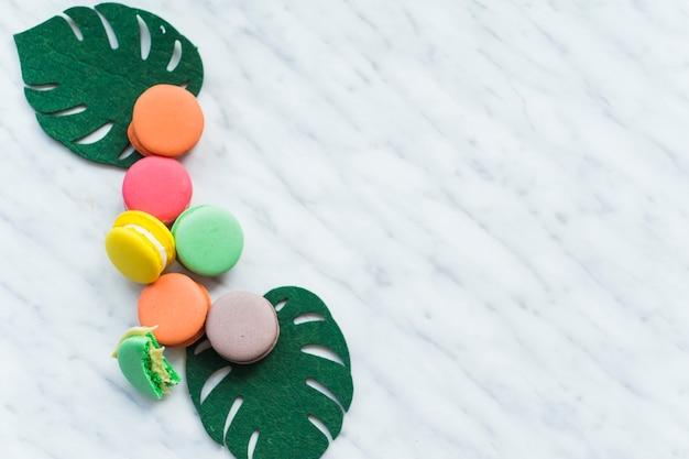Macaroons coloridos com monstera falso deixa sobre fundo de mármore branco