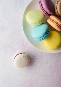 Macaroons coloridos de sobremesa francesa no prato, conceito mínimo plano leigo