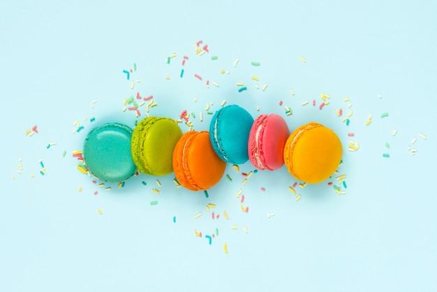 Macaroons coloridos dispostos como arco-íris no azul