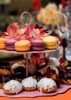 Macaroons coloridos e bolos deliciosos em uma bandeja bolos recém-coloridos em uma bandeja