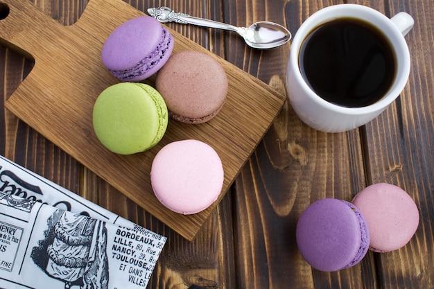 Macaroons coloridos e café no fundo de madeira