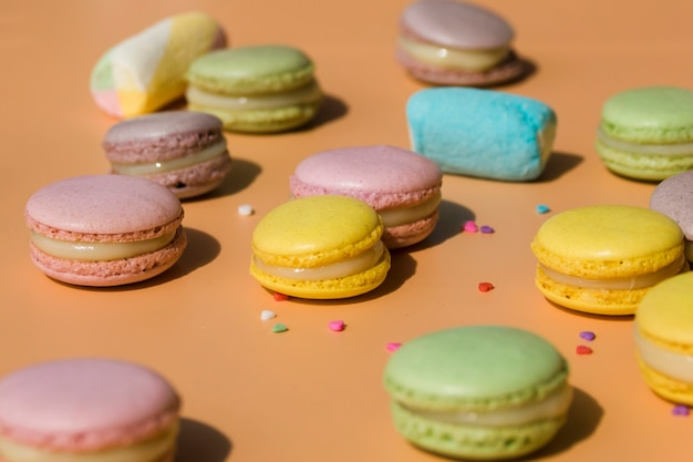 Macaroons coloridos e marshmallow com forma de coração polvilha