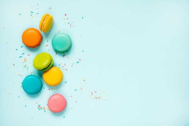 Macaroons coloridos e polvilha de açúcar dispostas sobre azul