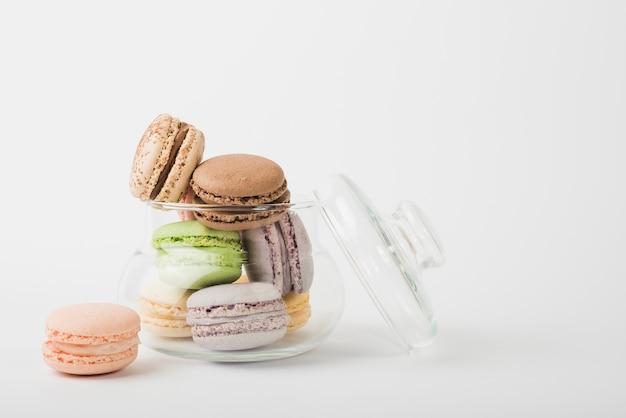 Macaroons coloridos em frasco de vidro aberto transparente no pano de fundo branco