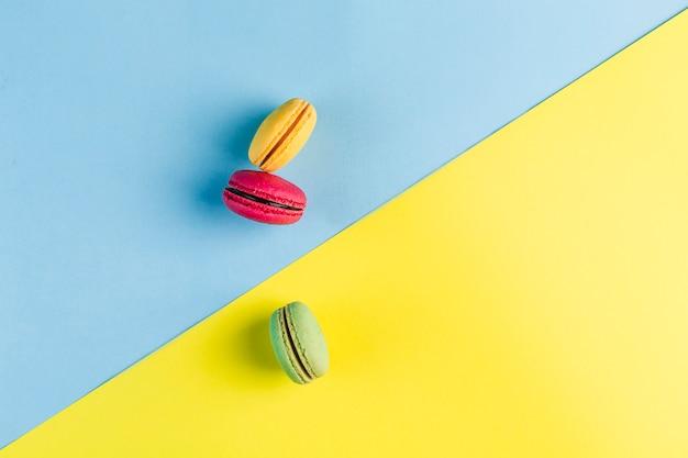Macaroons coloridos em um copyspace azul e amarelo, vista superior, flatley com copyspace
