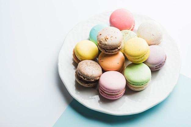 Macaroons coloridos no prato branco contra o fundo branco