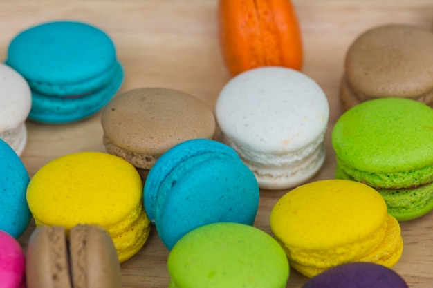 Macaroons coloridos no prato na mesa de madeira
