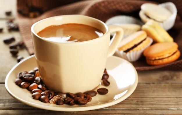 Macaroons coloridos suaves e café em caneca na mesa de madeira