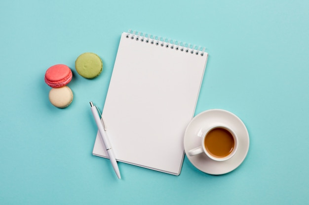 Macaroons com o bloco de notas em espiral, caneta e xícara de café sobre fundo azul