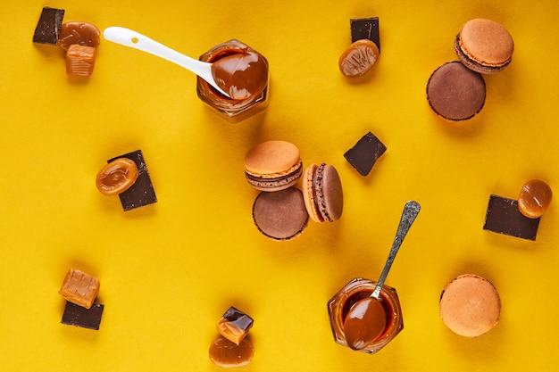 Macaroons com sabor a chocolate e caramelo em um fundo amarelo