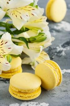 Macaroons de amarelo com flores no fundo
