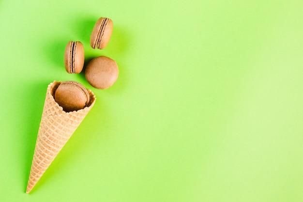 Macaroons de chocolate em um cone de waffle em um copyspace verde, vista superior, flatley com copyspace