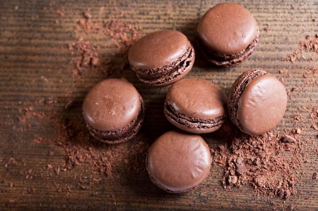 Macaroons de chocolate na mesa de madeira, vista superior