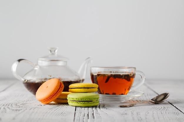 Macaroons de colorido com uma xícara de chá na mesa de madeira de cor
