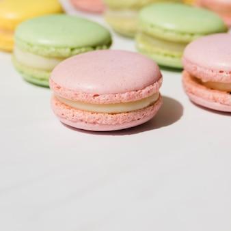 Macaroons de creme chantilly verde e rosa sobre fundo branco