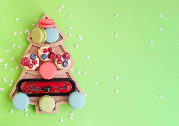 Macaroons de doces e bolos no prato em forma de árvore de natal