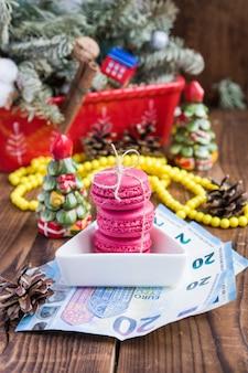 Macaroons de rosa e vinte euros com decorações de natal em fundo de madeira