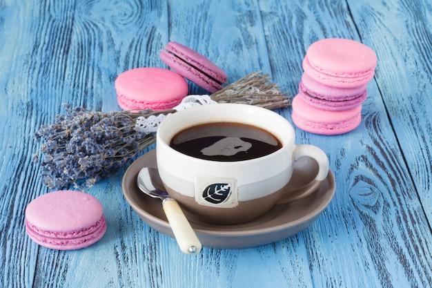 Macaroons de rosa e xícara de café perto de levanda seca