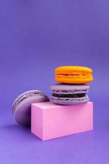 Macaroons de roxo e laranja em um pedestal. sobremesa francesa para o halloween. produtos de panificação de farinha de amêndoa.