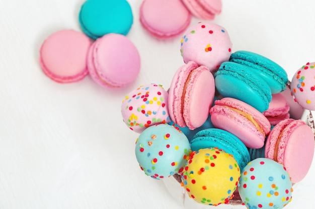 Macaroons doces coloridos e bolo aparece em tigela em madeira branca