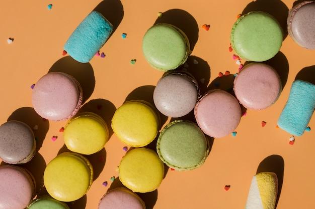 Macaroons e marshmallow com granulado no fundo marrom