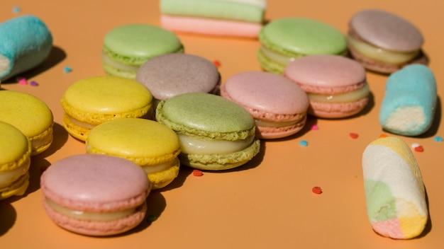 Macaroons e marshmallows em pano de fundo colorido