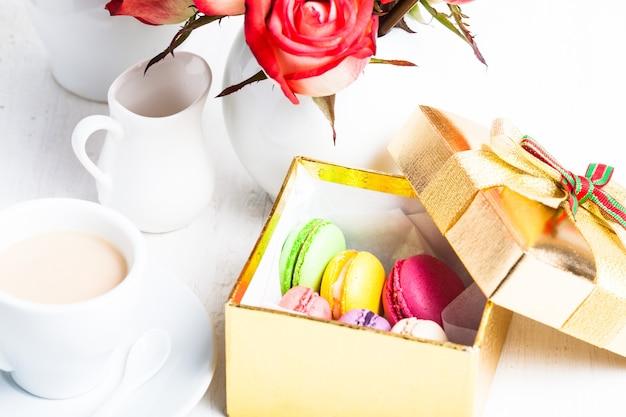 Macaroons em caixa de presente e rosas em vaso