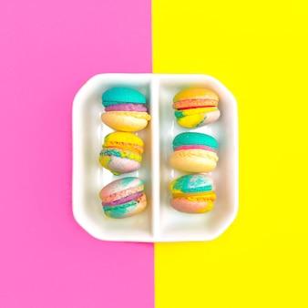 Macaroons em fundo colorido. design plano de alimentos