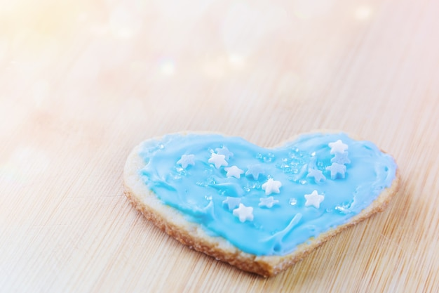 Macaroons festivos em forma de coração cobertos com glacê azul e polvilhados com estrelas de açúcar e cristais em uma placa de madeira