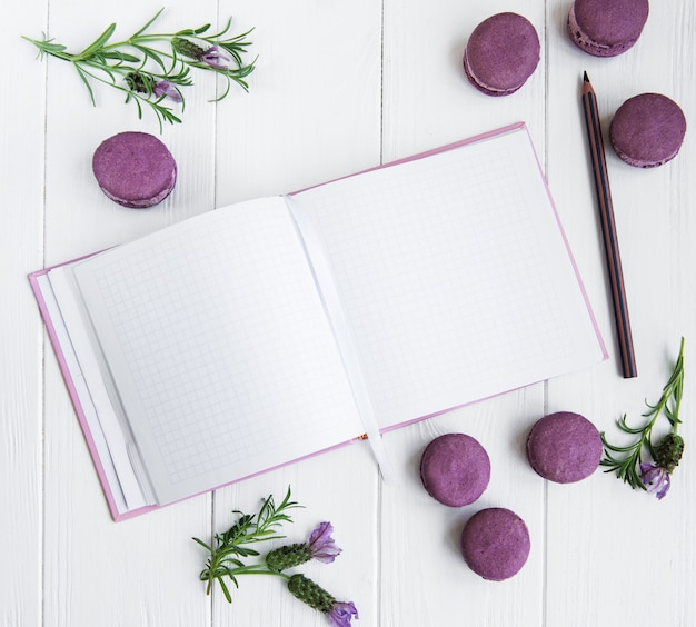 Macaroons franceses, caderno limpo e flores de lavanda