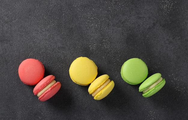 Macaroons franceses coloridos sobre fundo cinza escuro. vista de cima. espaço para texto