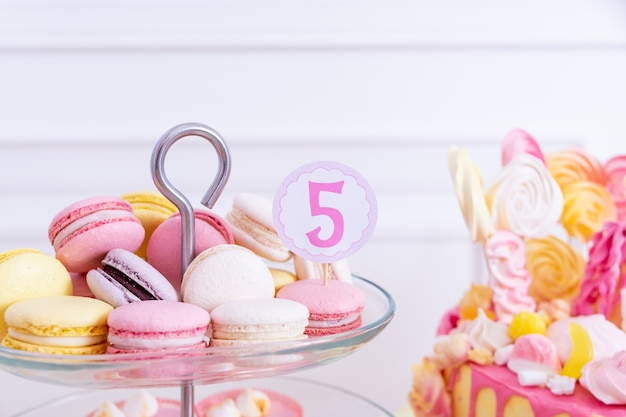 Macaroons franceses em um carrinho de bolo. bar doce com macaron, bolos, cheesecakes, bolo pop. macaroons coloridos na bandeja de servir. mesa de aniversário doce decorativa em cores brilhantes de amarelo, branco e rosa.