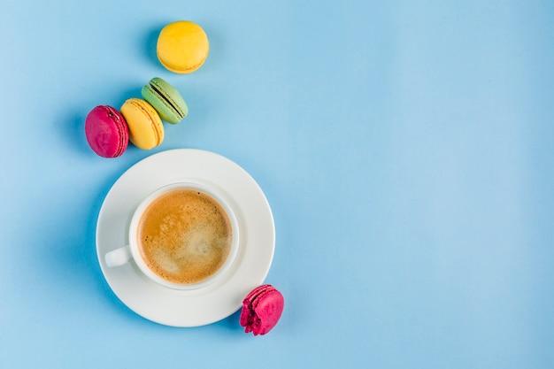 Macaroons multicoloridos com uma xícara de café branca em um copyspace azul, vista superior, plana leigos com copyspace