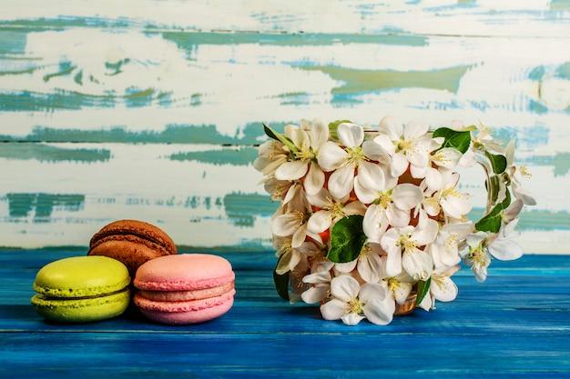 Macaroons multicoloridos e copo decorado com flores brancas
