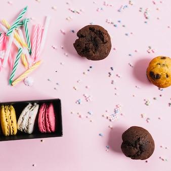 Macaroons multicoloridos; velas; muffins doces; pastel polvilha no fundo rosa