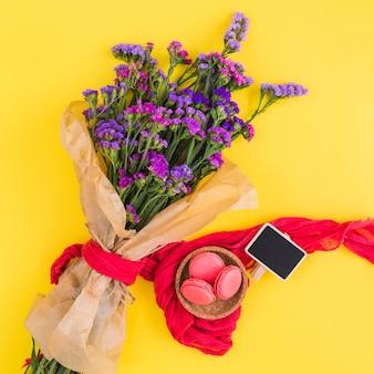 Macaroons na tigela; cartaz em branco; buquê de flores amarrado com roupas vermelhas contra fundo amarelo